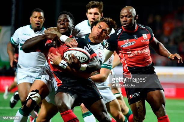 Oyonnaxs French wing Dug Codjo is challenged by Paus Fiji center Jale Vatubua during the French Top 14 rugby union match between Oyonnax and Pau on...