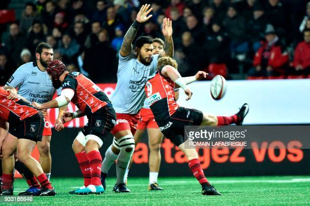 Oyonnax's South African scrumhalf James Hall tries to clear the ball next Toulon's French lock Romain Taofifenua during the French Top 14 rugby union...
