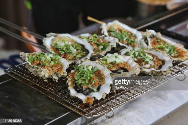 Oysters cooking on a small grill at a Chinese restaurant in the historic town of Unionville, Ontario, Canada.