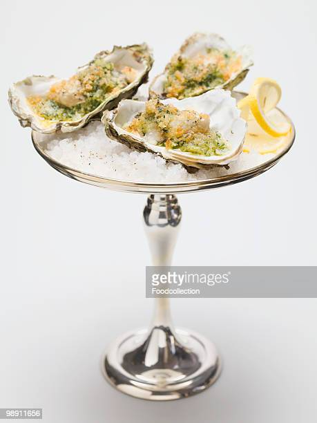 Oysters gratin on silver stand, close-up
