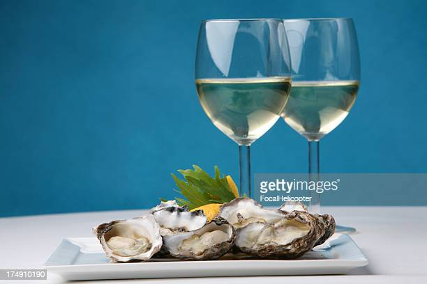 oysters on blue - oyster shell stock photos and pictures