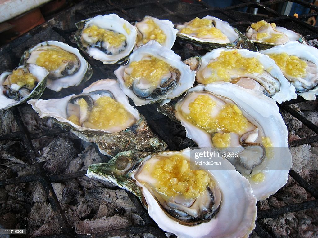BBQ oysters with garlic sauce : Stock Photo
