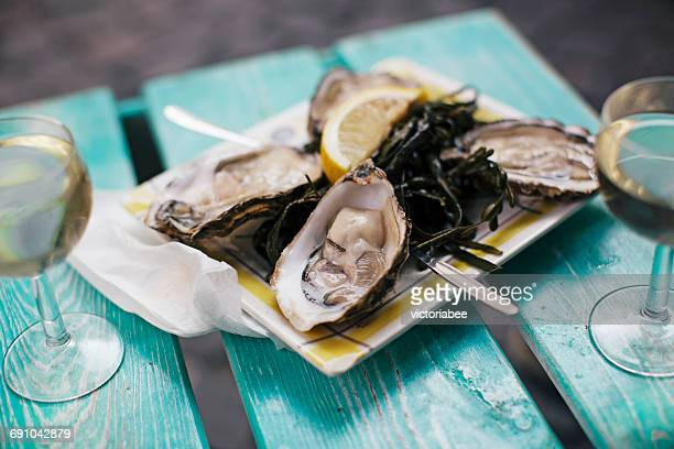 oysters with lemon and wine - oyster shell stock photos and pictures
