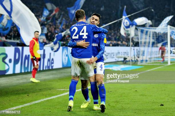Ozan Kabak of FC Schalke 04 celebrates scoring his sides second goal with teammate Bastian Oczipka during the Bundesliga match between FC Schalke 04...
