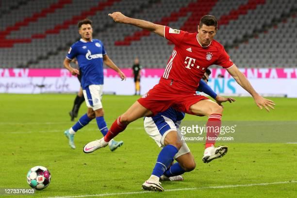Ozan Kabak of Schalke 04 tackles Robert Lewandowski of Bayern Munich during the Bundesliga match between FC Bayern Muenchen and FC Schalke 04 at...