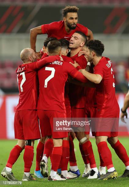 Ozan Tufan of Turkey celebrates with teammates after scoring his team's first goal during the international friendly match between Germany and Turkey...