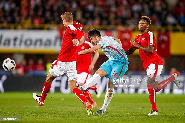 Ozan Tufan of Turkey competes for the ball with Stefan Ilsanker and David Alaba of Austria during the international friendly match between Austria...
