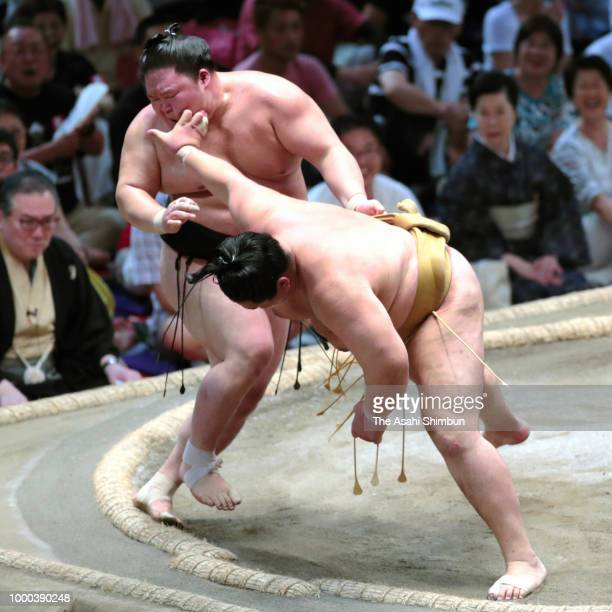 Asanoyama pushes Ishiura out of the ring to win on day nine of the Grand Sumo Nagoya Tournament at the Dolphin's Arena on July 16 2018 in Nagoya...