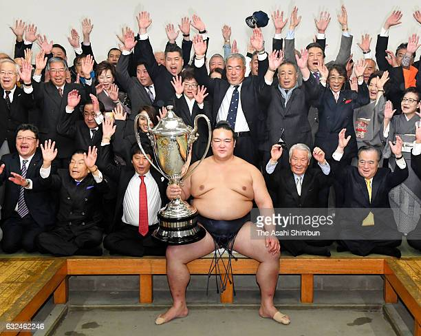 Ozeki Kisenosato pose with the trophy while his supporters make banzai cheers after winning the tournament for the first time at the dressing room...