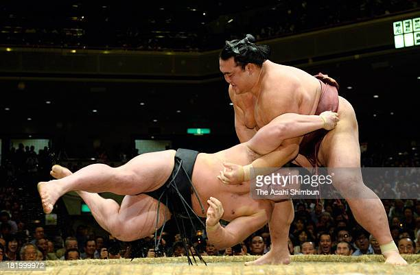 Ozeki Kisenosato throws Mongolian yokozuna Harumafuji whose real name is Altangadasyn Khuchitbaatar during day twelve of the Grand Sumo Autumn...