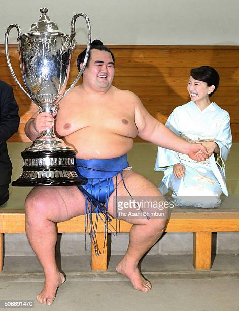 Ozeki Kotoshogiku holding the trophy celebrates with his wife Yumi after winning the tournament at the dressing room during day fifteen of the Grand...