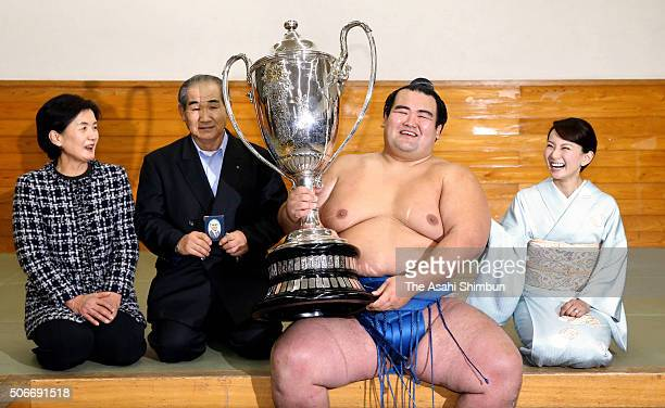 Ozeki Kotoshogiku holding the trophy celebrates with his wife Yumi father Kazunori and mother Mieko after winning the tournament at the dressing room...