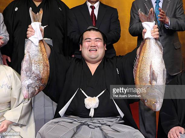 Ozeki Kotoshogiku holds red snappers to celebrate after winning the tournament during day fifteen of the Grand Sumo New Year Tournament on January 24...