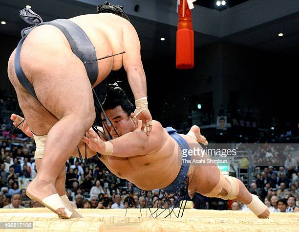 Ozeki Kotoshogiku pushes Toyonoshima out of the ring to win during day five of the Grand Sumo Kyushu Tournament at Fukuoka Convention Center on...
