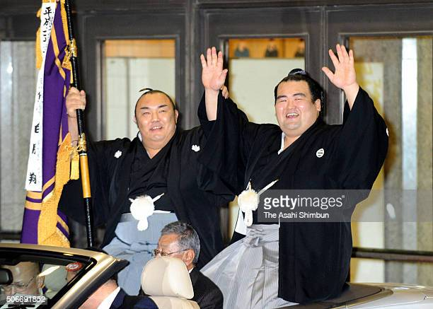 Ozeki Kotoshogiku waves to fans during the victory parade to celebrate after winning the tournament during day fifteen of the Grand Sumo New Year...