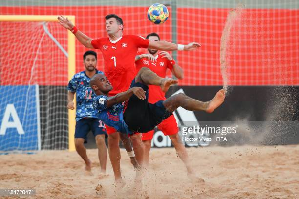 Ozu Moreira of Japan struggles for the ball with Sandro Spaccarotella of Switzerland during the FIFA Beach Soccer World Cup Paraguay 2019 group A...