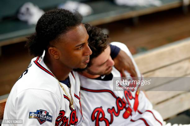 Ozzie Albies and Dansby Swanson of the Atlanta Braves react after their teams 13-1 loss to the St. Louis Cardinals in game five of the National...