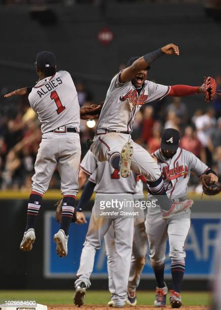 Ozzie Albies and Ronald Acuna Jr #13 of the Atlanta Braves celebrate after defeating the Arizona Diamondbacks in the tenth inning of the MLB game at...