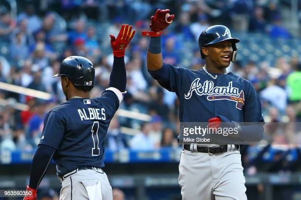 Ozzie Albies and Ronald Acuna Jr #13 of the Atlanta Braves celebrate after scoring on an RBI double by Freddie Freeman in the first inning against...