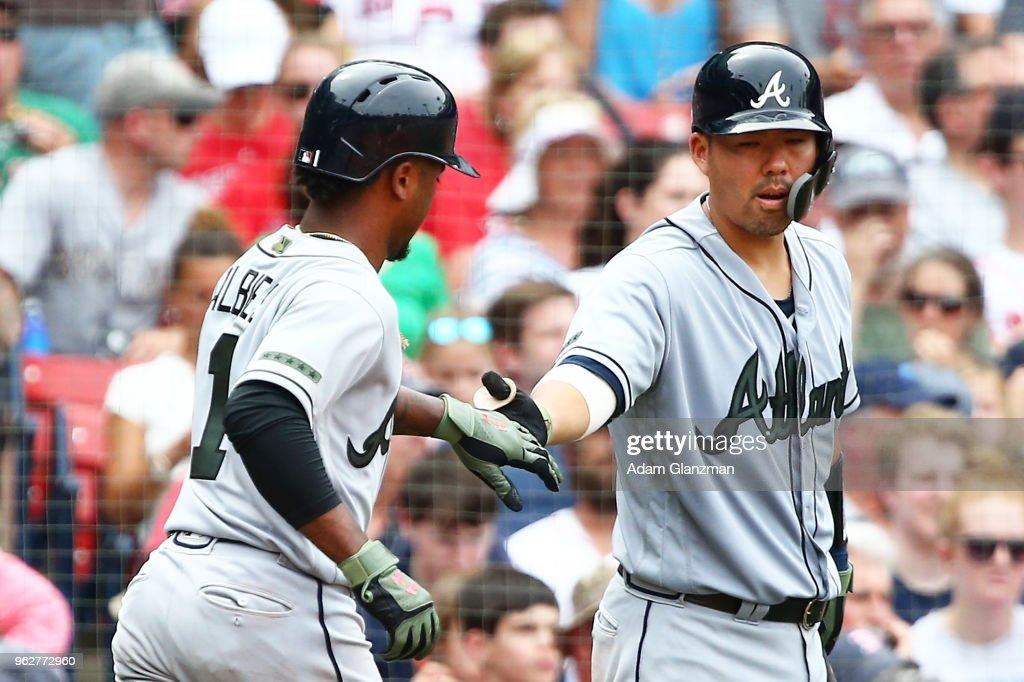 Ozzie Albies #1 high fives Kurt Suzuki #24 of the Atlanta Braves after scoring in the fourth inning of a game against the Boston Red Sox at Fenway Park on May 26, 2018 in Boston, Massachusetts.