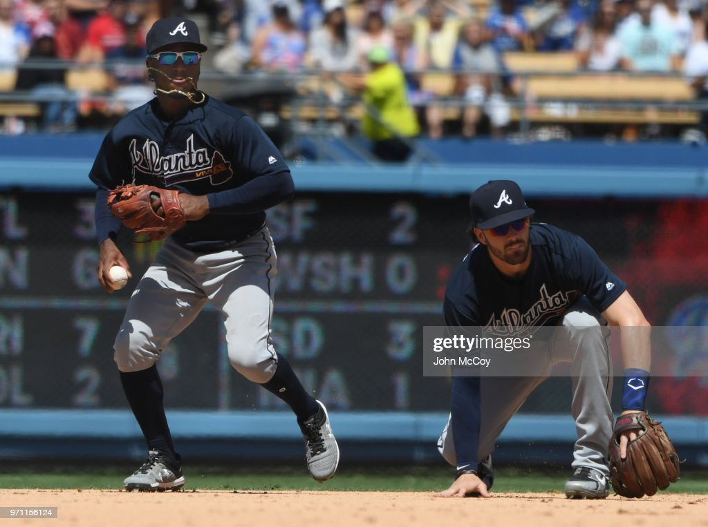 Ozzie Albies #1, left, of the Atlanta Braves and Dansby Swanson #7 are not able to handle a single hit by Ross Stripling #68 of the Los Angeles Dodgers in the sixth inning at Dodger Stadium on June 10, 2018 in Los Angeles, California.