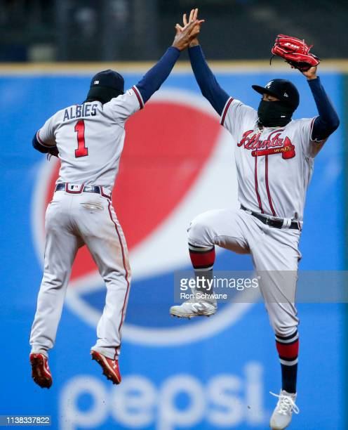 Ozzie Albies of the Atlanta Braves and Ronald Acuna Jr #13 celebrate a 87 victory over the Cleveland Indians of Game 2 of a doubleheader at...