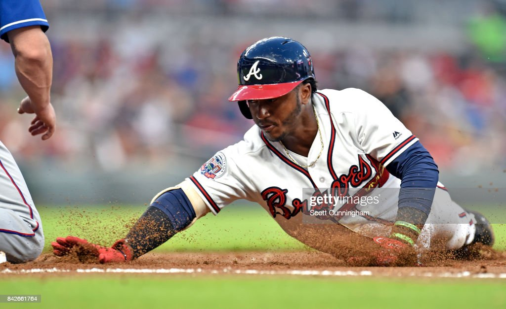 Ozzie Albies #1 of the Atlanta Braves dives back to first base during the first inning against the Texas Rangers at SunTrust Park on September 4, 2017 in Atlanta, Georgia.