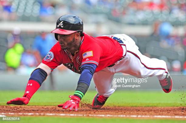 Ozzie Albies of the Atlanta Braves dives back to first base during the first inning against the Miami Marlins at SunTrust Park on September 10 2017...