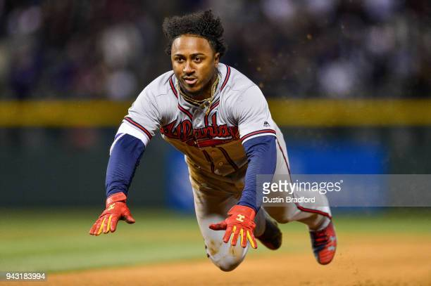 Ozzie Albies of the Atlanta Braves dives back to first base to avoid being doubled off in the ninth inning of a game against the Colorado Rockies at...