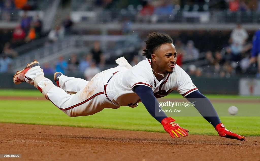 Ozzie Albies #1 of the Atlanta Braves dives safely for third base on his triple hit in the eighth inning against the Chicago Cubs at SunTrust Park on May 16, 2018 in Atlanta, Georgia.