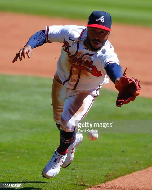 Ozzie Albies of the Atlanta Braves fields and tosses to first in the sixth inning of Game One of the National League Wild Card Series against the...