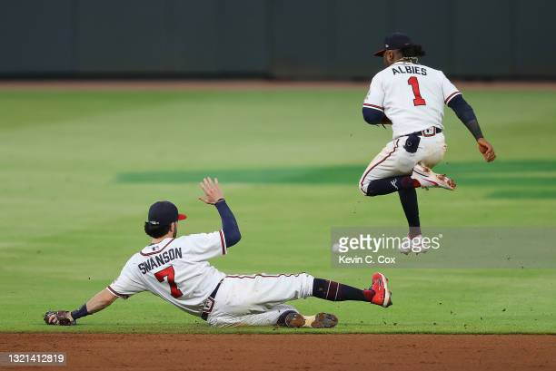 Ozzie Albies of the Atlanta Braves leaps over a sliding Dansby Swanson as a RBI single gets through them by Trea Turner of the Washington Nationals...
