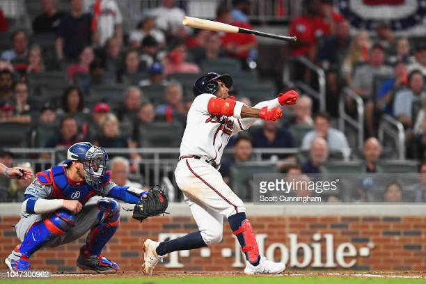 Ozzie Albies of the Atlanta Braves loses his bat as he swings in the sixth inning against the Los Angeles Dodgers during Game Three of the National...