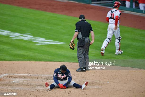 Ozzie Albies of the Atlanta Braves sits at home plate after getting tagged out by J.T. Realmuto of the Philadelphia Phillies in the 10th inning on...