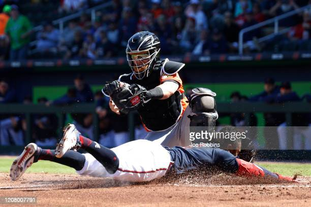 Ozzie Albies of the Atlanta Braves slides at home plate to score a run ahead of the throw to Chance Sisco of the Baltimore Orioles in the first...