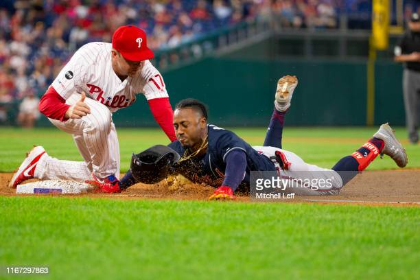 Ozzie Albies of the Atlanta Braves slides back safely past the tag of Rhys Hoskins of the Philadelphia Phillies after hitting a single in the top of...