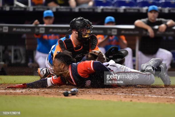 Ozzie Albies of the Atlanta Braves slides into home plate during the eighth inning against the Miami Marlins at Marlins Park on August 26 2018 in...