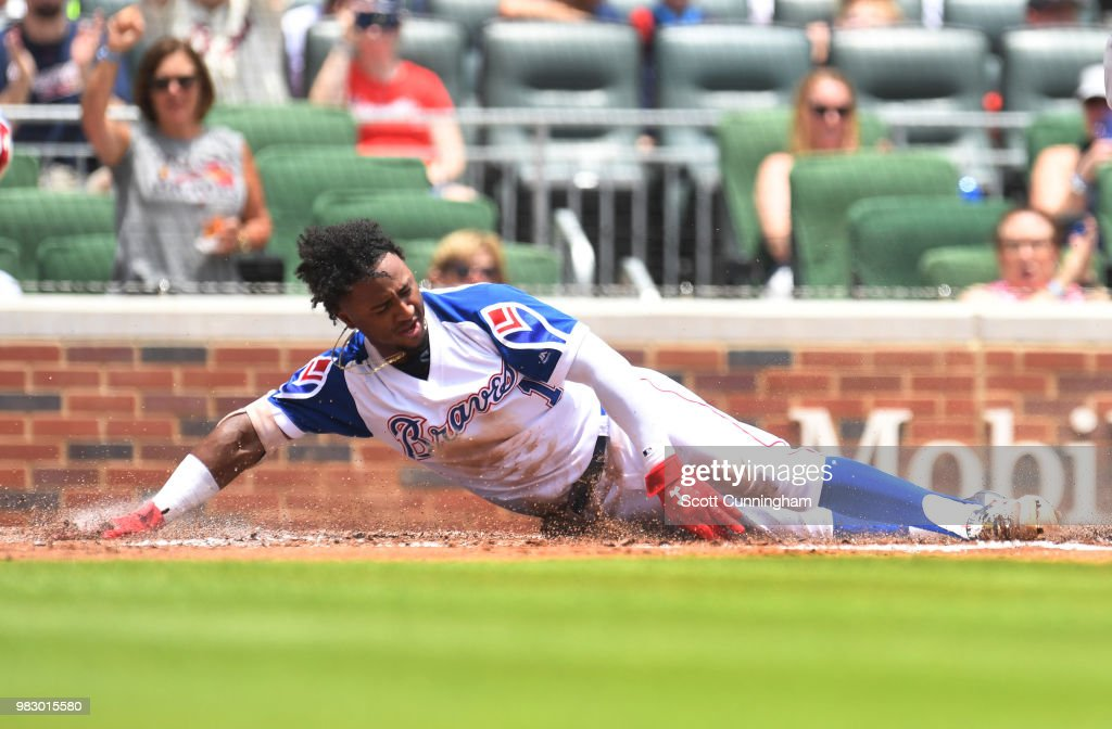 Ozzie Albies #1 of the Atlanta Braves touches home plate to score a first inning run against the Baltimore Orioles at SunTrust Park on June 24, 2018 in Atlanta, Georgia.