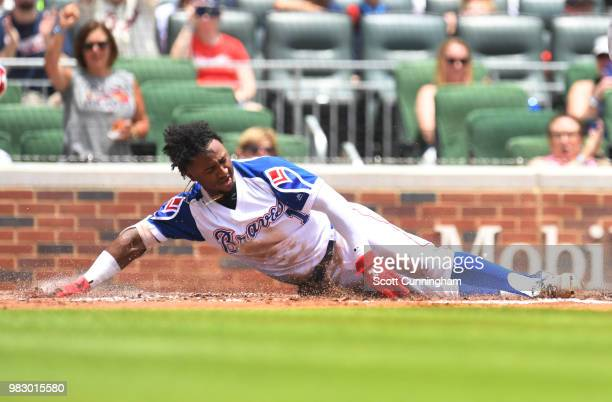 Ozzie Albies of the Atlanta Braves touches home plate to score a first inning run against the Baltimore Orioles at SunTrust Park on June 24 2018 in...