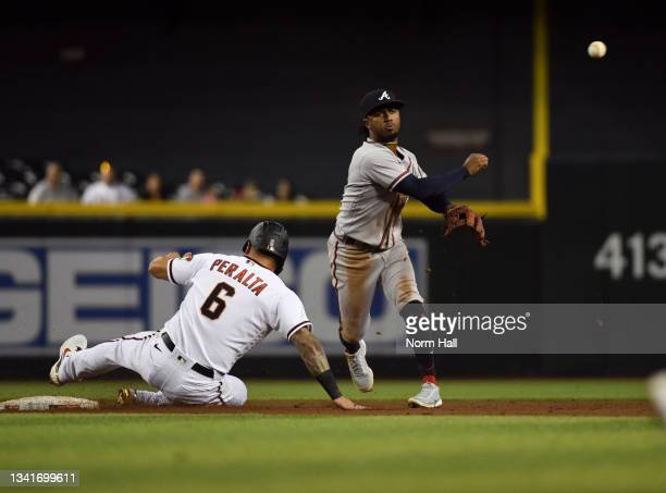 Ozzie Albies of the Atlanta Braves turns a double play on a ground ball hit by Carson Kelly of the Arizona Diamondbacks as David Peralta is forced...