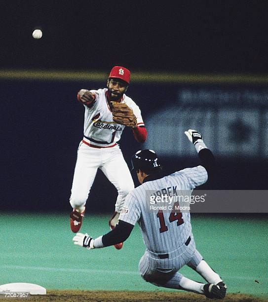 Ozzie Smith of the St. Louis Cardinals throws to first base for a double play as Kent Hrbek of the Minnesota Twins is forced at second base during...