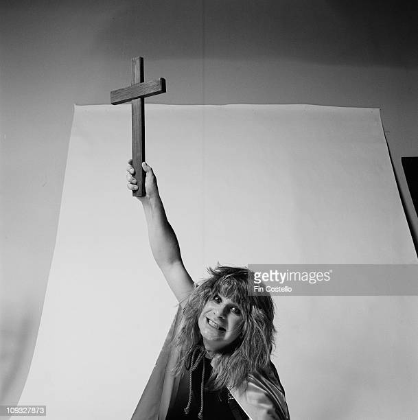 Ozzy Osbourne posed in a studio holding a crucifix recreating the cover shot of the Blizzard Of Ozz album session
