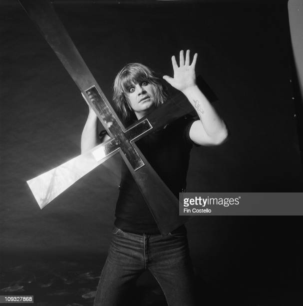 Ozzy Osbourne posed in a studio holding a large cross recreating the cover shot of the Blizzard Of Ozz album session