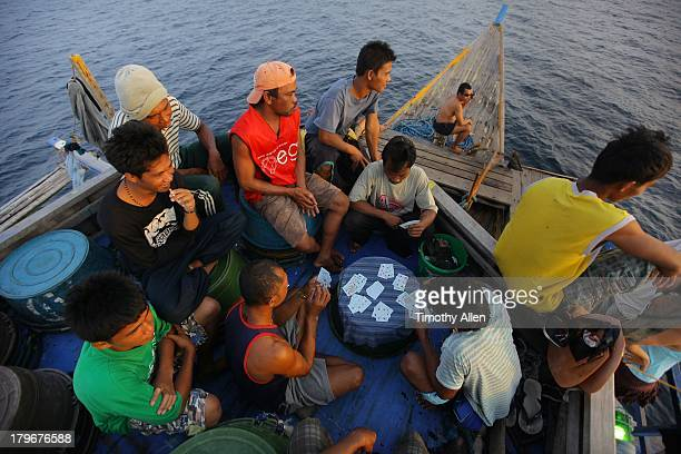 Pa Aling fishermen play cards on the boat deck