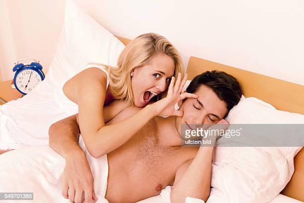 Paar hat Spass im Bett. Lachen, Freude und Erotik im Schlafzimmer