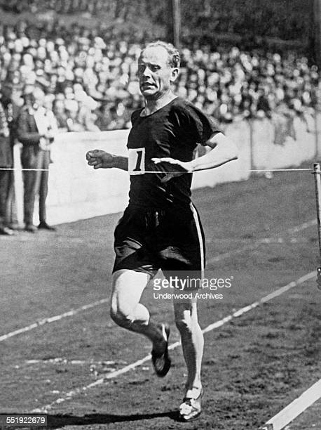 Paavo Nurmi, the 'Flying Finn' in an attempt to break his own four mile world record of 19 minutes, 15.6 seconds, at the annual Stamford Bridge meet,...