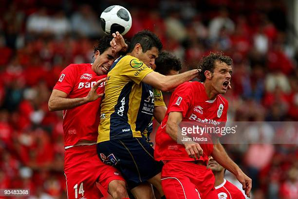 Pablo Aguilar of San Luis vies for the ball with Edgar Duenas and Diego Novaretti of Toluca during their quarterfinals match as part of the 2009...