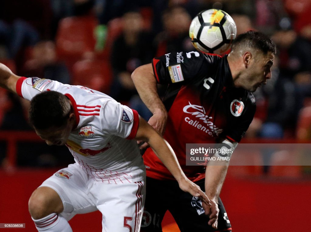 Pablo Aguilar (R) of Tijuana from Mexico vies for the ball with Connor Lade (L) of New York from United States during the first leg of the CONCACAF Champions League quarterfinals match at Caliente Stadium in Tijuana, Mexico on March 6, 2018. /