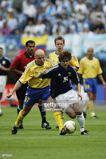 Pablo Aimar of Argentina is challenged by Magnus Svensson of Sweden during the Argentina v Sweden Group F World Cup Group Stage match played at the...