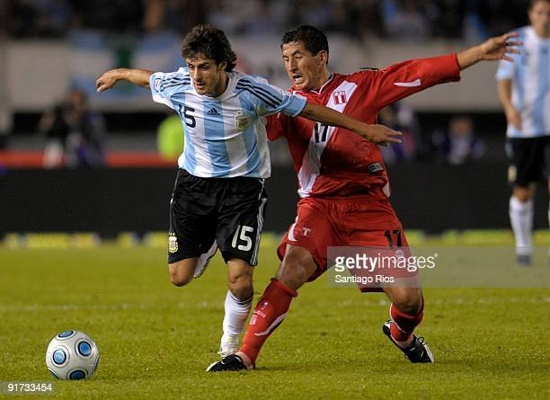 Pablo Aimar of Argentina vies for the ball with Johan Fano of Peru during their match as part of the FIFA 2010 World Cup Qualifier at Monumental...